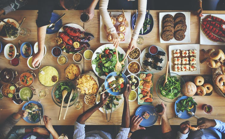 A table of friends eating a variety of food dishes