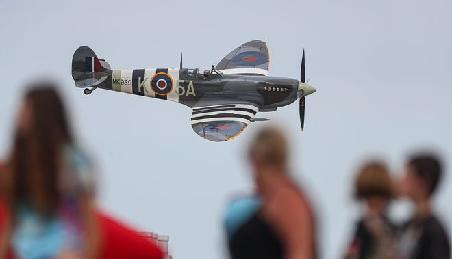 A WWII Spitfire flies by a crowd of people Friday, July 30, 2021 during the 2021 Airventure air show on the EAA grounds in Oshkosh, Wisconsin.